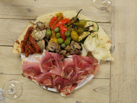 Still life, food and drink, holidays concept. Assortment italian antipasti, jamon, prosciutto, on a plate, Top View