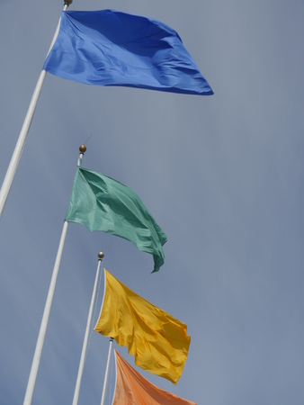 flagpoles: Flags of different colors on flagpoles