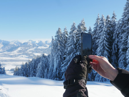woman photographing a winter landscape with her smartphone Фото со стока
