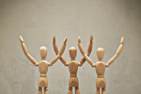 Three wooden mannequin hands up as winners Stock Photo
