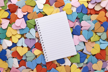 yellow notepad: Colorful Handmade origami hearts background with notepad Stock Photo