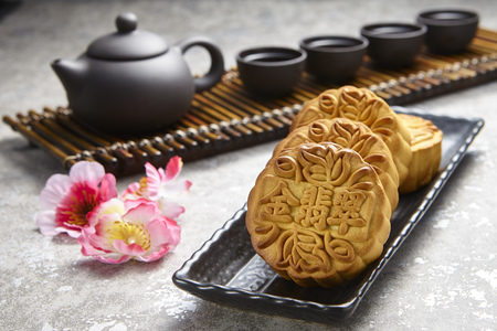 Golden Emerald mooncake on wooden table. Chinese mid autumn festival foods