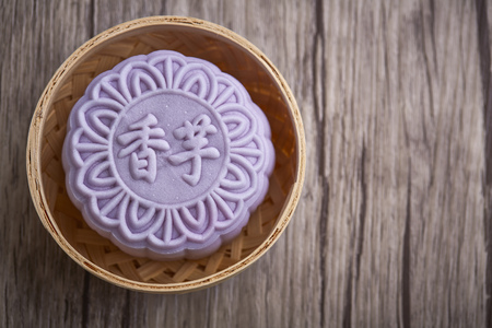 Chinese mid autumn festival foods. Snow skin mooncake on wooden table with text Purple