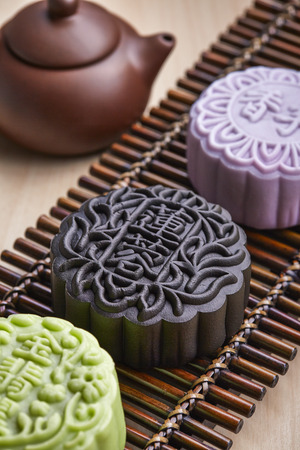 Chinese mid autumn festival foods. Snow skin mooncake on wooden table with text Green