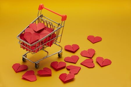 Trolley with red heart on yellow background, top view with copy space