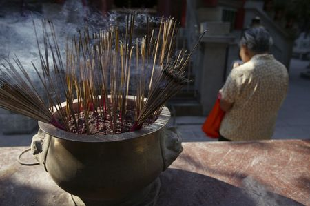 worshipping: A woman worshipping at a temple in Hong Kong. Stock Photo
