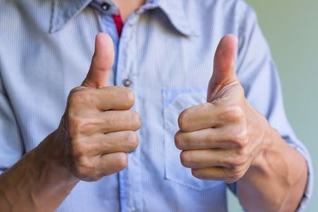 Man is showing double thumbs up