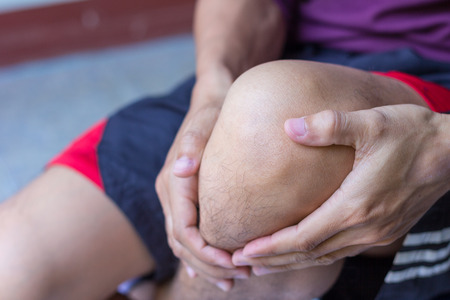 emotional pain: man with knee pain and feeling bad Stock Photo