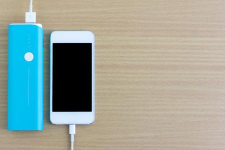 energia electrica: Smartphone est� cargando con el banco de potencia Foto de archivo