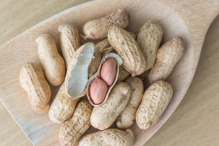 arachis: close up wood ladle full of peanuts Stock Photo