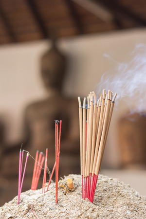 Incense sticks with blur statue photo