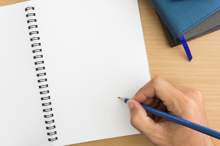 note notebook: hand is writing on  blank notebook