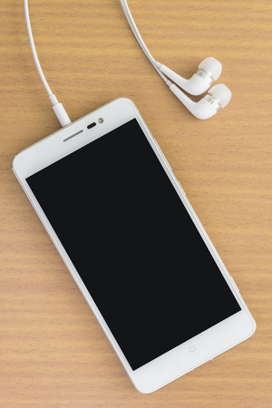 earphone: smart phone with earphone on wood table Stock Photo
