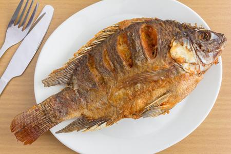 plato de pescado: El pescado frito en la mesa de madera