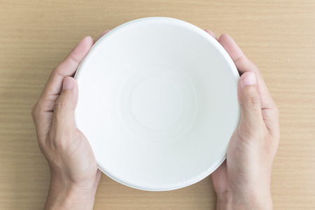 Pohled shora na člověka ruku s prázdnou miskou