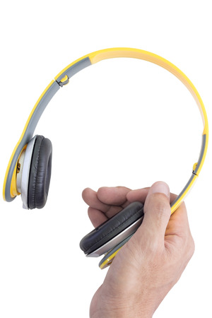decibels: right hand holding yellow headphone on white background