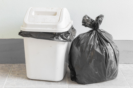 Black garbage bags and dirty white bin
