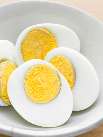 egg shape: half of boil egg in white bowl Stock Photo