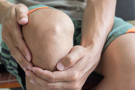 hand pain: man with knee pain and feeling bad Stock Photo