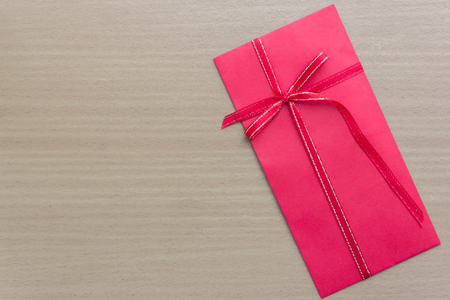 red envelope with ribbon bow on table Standard-Bild