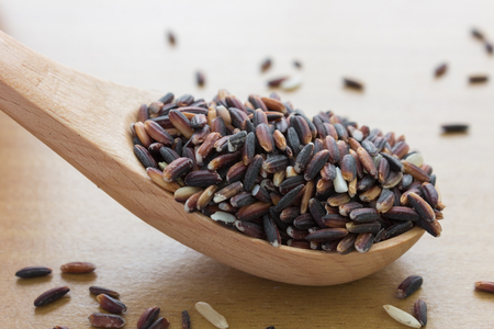 close up shot of black rice in wooden spoon Stock Photo