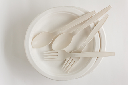 Fork and spoon with disposable paper plate for party