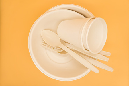 paper plate with fork and spoon on orange background in top view