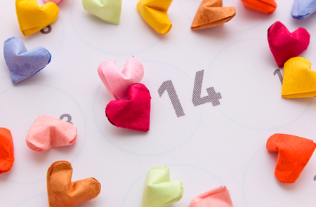 scattered in heart shaped: colorful paper hearts in top view with calendar Stock Photo