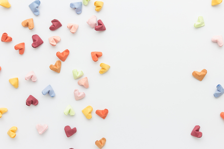 scattered in heart shaped: color paper heart on white  in top view Stock Photo