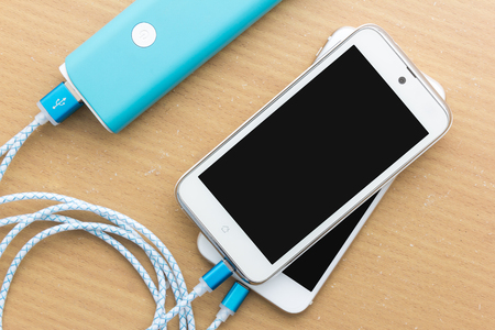 amp: Smartphone is charging with power bank in top view