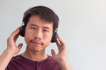 radio activity: Happy asian man is listening to the music