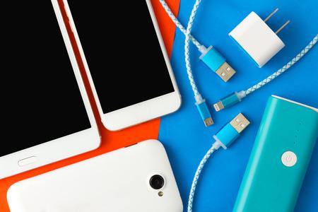 블루투스 및 오렌지 배경에서 상단보기에서 스마트 폰 및 태블릿을위한 USB 충전 케이블