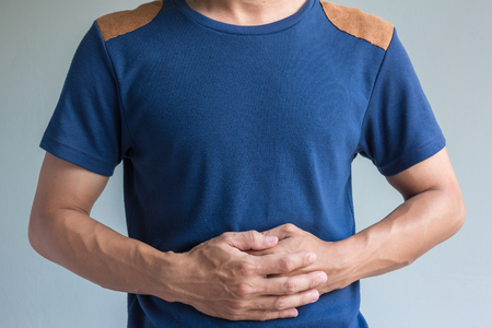 man have stomachache on gray background Stock Photo