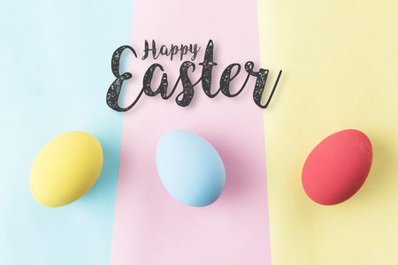 happy easter word with pastel easter eggs in top view