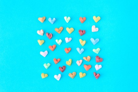 Colorful paper heart on green in top view Stockfoto