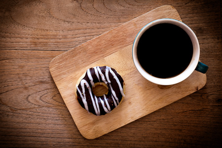 donut style: breakfast with donut and coffee cup in coffee shop - Dark  style effect picture Stock Photo