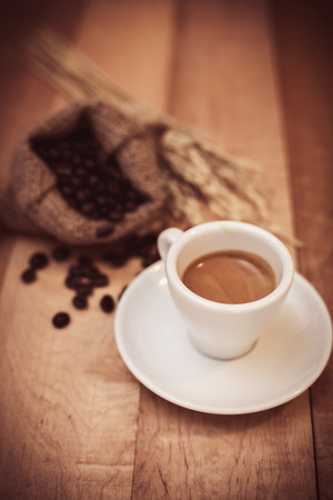 Hot coffee and coffee beans on a wooden table with vintage tone.