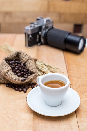 buccal: Hot coffee and coffee beans and camera vintage on a wooden table Stock Photo
