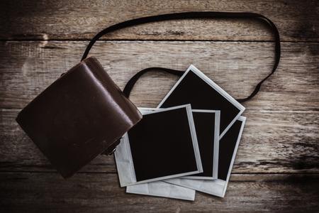 Vintage polaroid film camera on a wooden table.