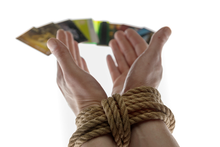 tied with a rope hands and credit cards on white background