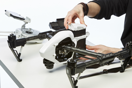 mechanization: a man sits with a drone behind a table Stock Photo