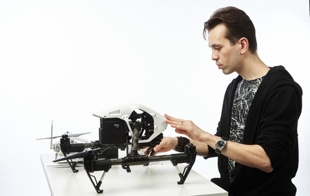 a man sits with a drone behind a table Stock Photo