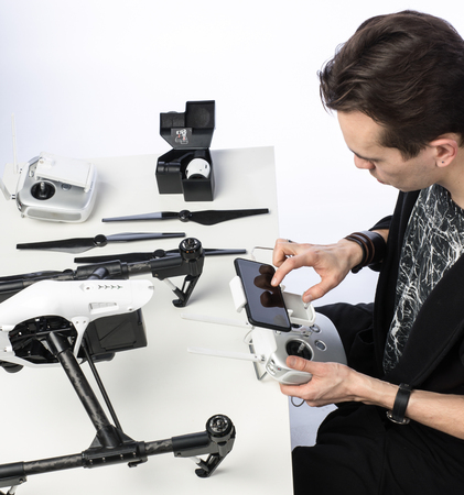 pastime: a man sits with a drone behind a table Stock Photo
