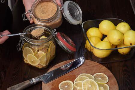 cuts lemons and pours them cane sugar