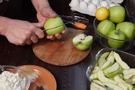 The man prepares in kitchen of apple pie with citrus