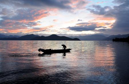 boatman: Boatman in a boat at Lugu lake Stock Photo
