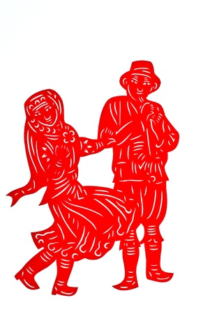 Chinese Minority Lad and Girl Dancing.A traditional Chinese paper cutting of minority lad and girl, both in traditional clothing, dancing happily. Stock Photo - 9294458