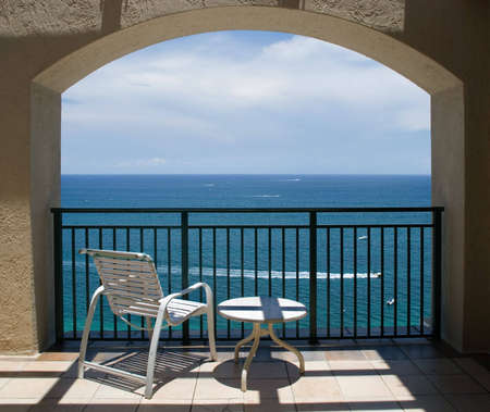 An inviting view of the ocean and a boat through an arch of a balcony. photo