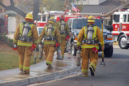 Fire fighters carrying their tools and equipment head to a house on fire.
