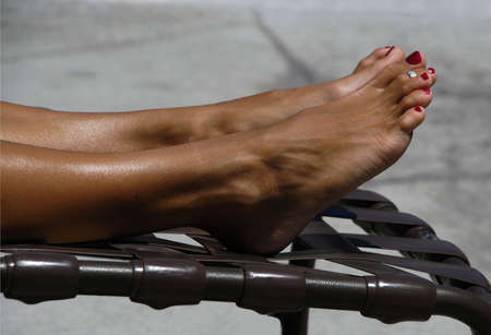 Legs and feet of a woman getting a tan on a lounge chair.